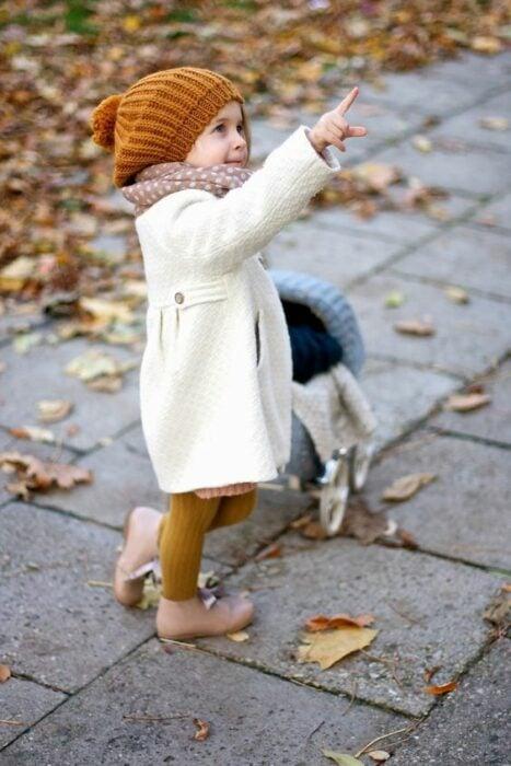 Niña pequeña vistiendo abrigo blanco, gorrito naranja, mallas amarillo mostaza y botas beige