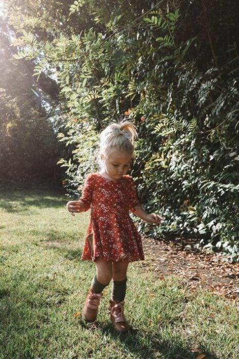 Niña rubia con coleta alta vistiendo vestido floreado color naranja con calcetas negras y botas cafés