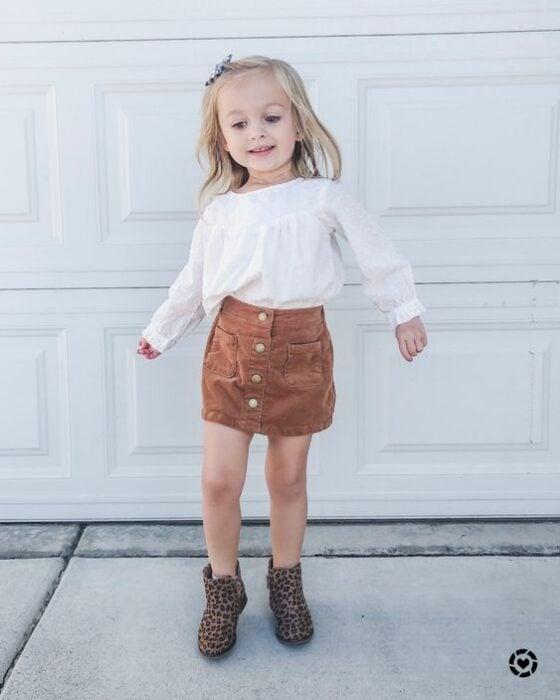 Niña pequeña rubia con blusa blanca, falda naranja de pana y botas cafés