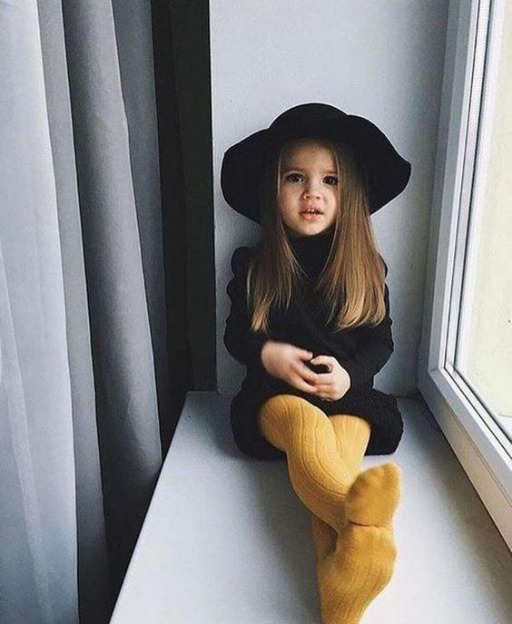 Niña de cabello castaño largo y liso sentada en una ventana con las piernas extendidas mientras viste un vestido negro, mallas amarillas y sombrero negro