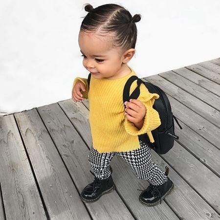Niña pequeña de cabello negro peinado en chonguitos con suéter amarillo, pantalón de cuadros y zapatos negros