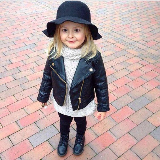 Niña rubia de cabello largo y suelto con sombrero negro, chamarrita negra de cuero, suéter blanco y botas negras altas