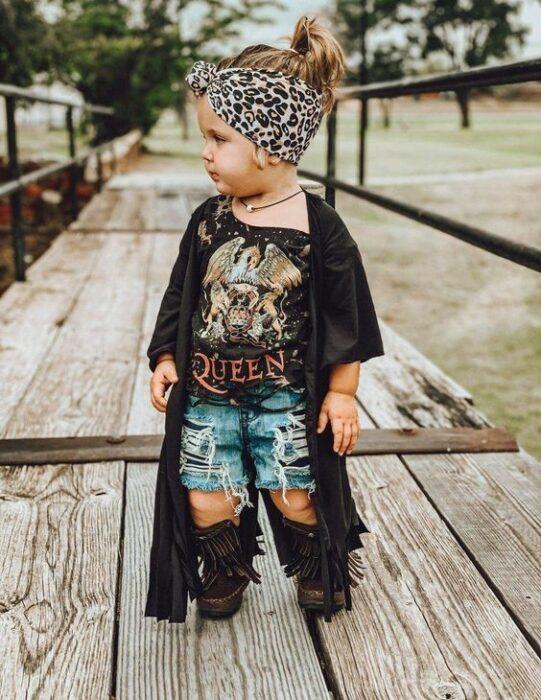Bebé rubia con banda de animal print en la cabeza con short de mezclilla botas negras altas, blusa rockera y kimono negro