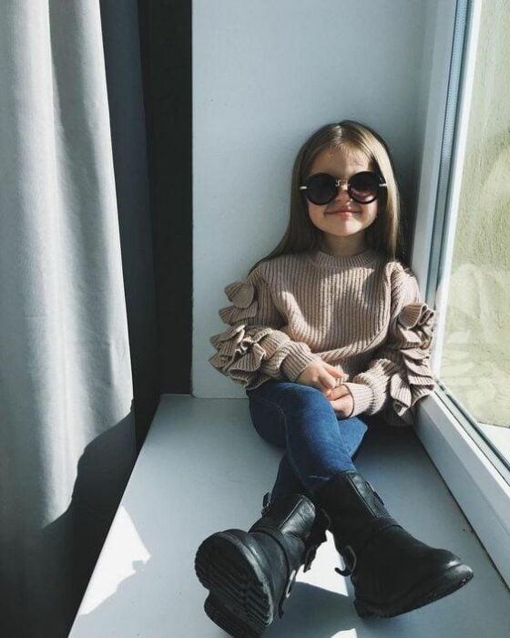 Niña De cabello castaño largo sentada en la ventana vistiendo suéter beige, pantalón de mezclilla, botas engras altas y lentes negros de sol