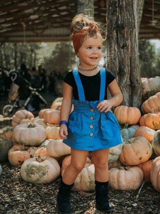 Niña rubia con banda naranja en la cabeza con blusa negra y falda de mezclilla y de fondo unas calabazas