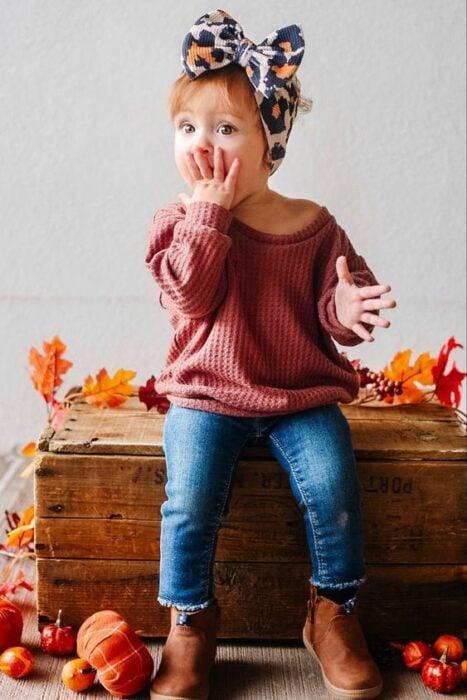 Niña pequeña con banda de animalt print en la cabeza con suéter rojo y jeans azul marino sentiada en una caja de madera
