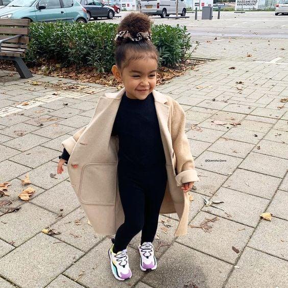 Niña pequeña de cabello rizado peinado en un chongo alto con blusa y pantalón negros, tenis blancos y abrigo beige