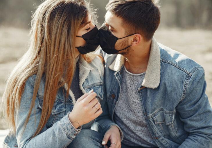 Pareja enamorada con cubrebocas dándose un beso; el amor te hace resistente al Covid