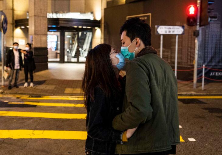 Pareja enamorada en la calle con cubrebocas dándose un beso; el amor te hace resistente al Covid