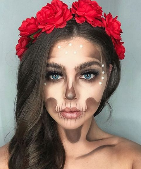 Girl with a catrina makeup wearing a crown of red roses