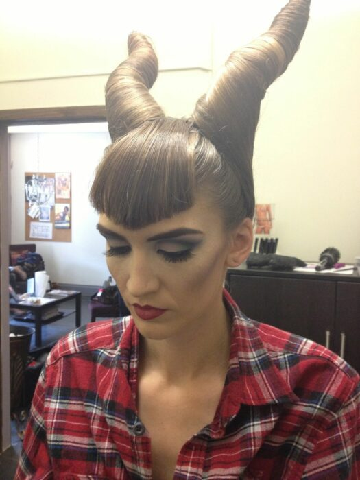 Girl with hair braided in two horns like those of malefica