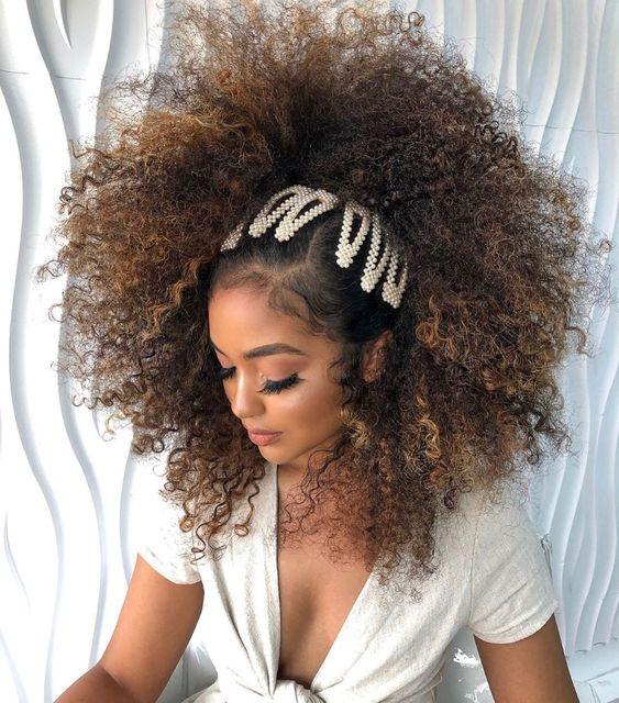 Chica con cabello rizado peinado con broches de perlas