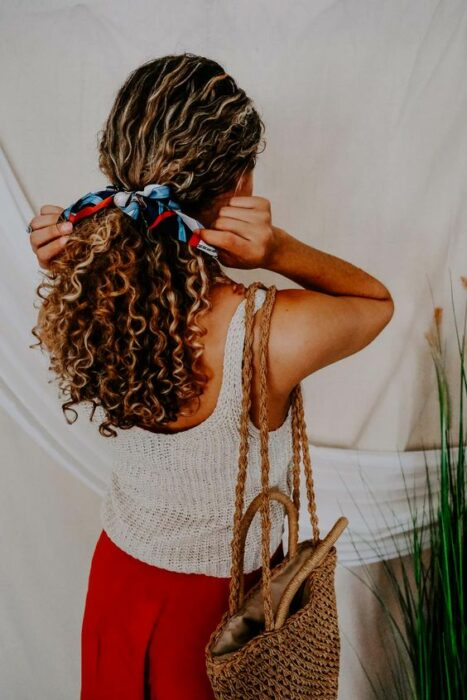 Girl with curly hair combed with a scarf