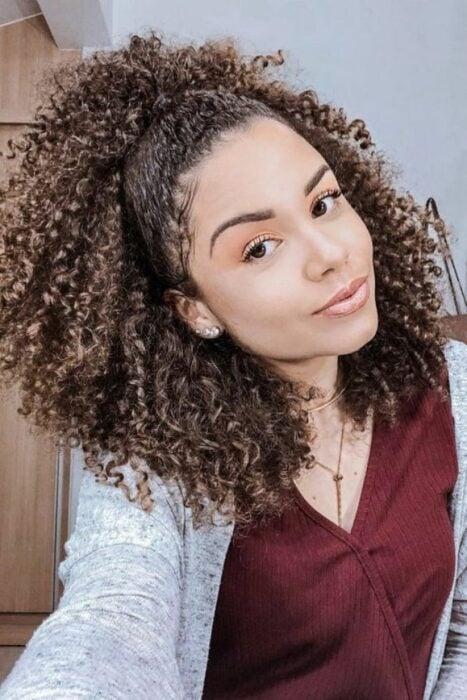 Chica con cabello rizado sellado al frente