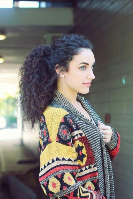 Chica con cabello rizado peinado en coleta alta