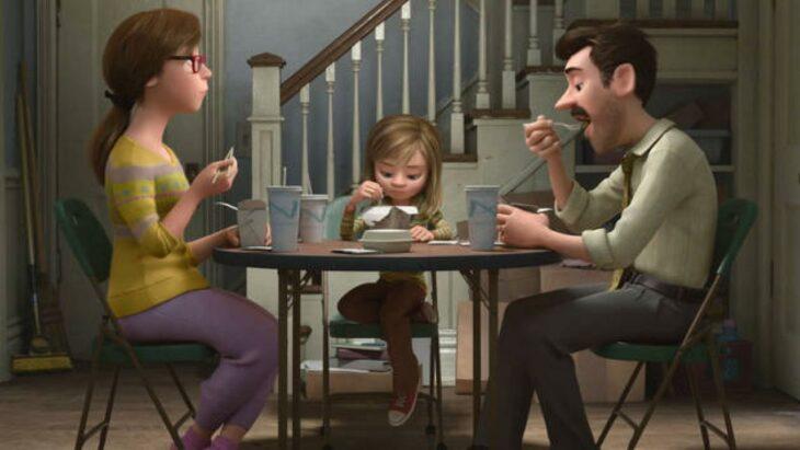 Escena de la película Intensamente. Riley comiendo en una mesa junto a sus padres