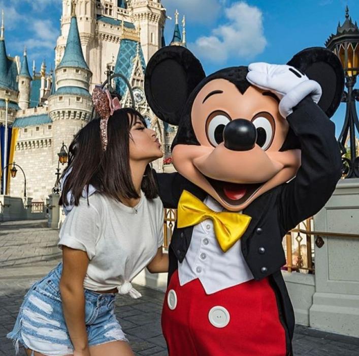 Chica de melena corta café con blusa blanca y shorts de mezclilla besando a Mickey MOuse