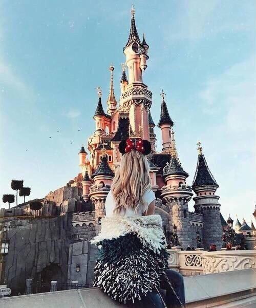 Chica rubia de cabello rubio rizado con orejas de Mickey Mouse mirando el castillo de Disney