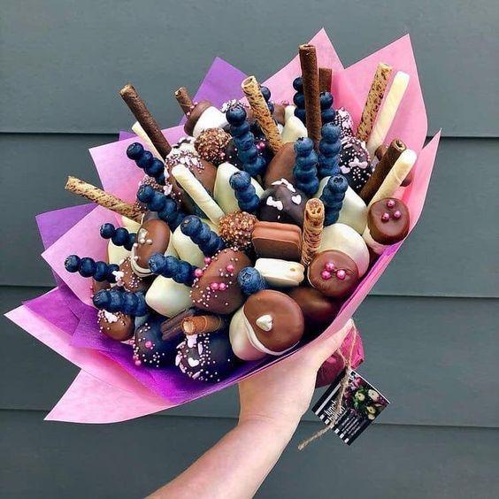 Ramos de galletas, arándanos y palillos crujientes envuelto en papel china color rosa y morado