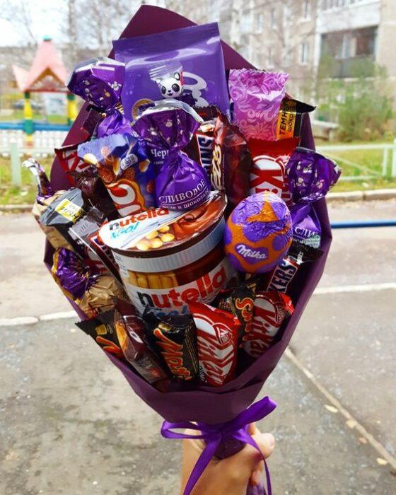 Ramos de chocolates con un bote de Nutella envueltos en una cartulina morada con un moño morado también