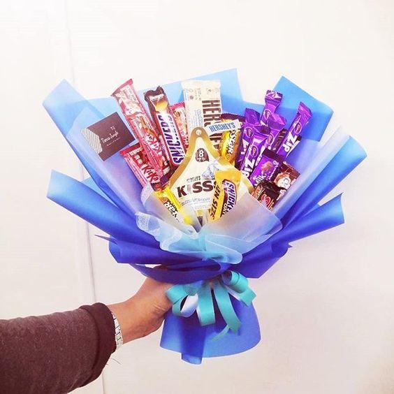 Ramos de chocolates, kisses y hersheys envuelto en papel azules con moño verde aqua