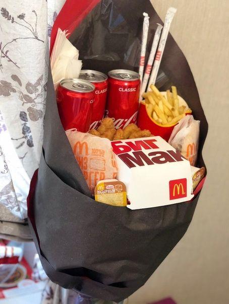 Ramos de papas hamburguesas y nuggets de McDonalds con dos coca colas de lata envueltos en papel negro