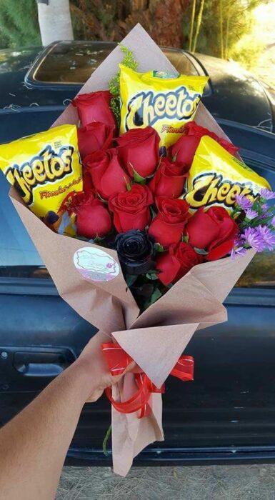 Ramos de rosas rojas y cheetos envuelto en papel café con una moño rojo