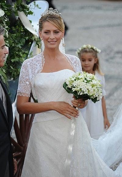 Tatiana Batnik el día de su boda luciendo un vestido blanco de encaje con un ramo de novia con flores blancas