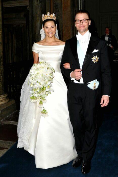 Victoria de Suecia el día de su boda luciendo un vestido blanco de encaje con un ramo de novia con flores blancas