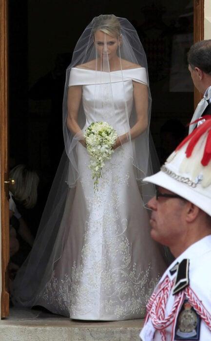 Charlene de mónaco el día de su boda luciendo un vestido blanco de encaje con un ramo de novia con flores blancas
