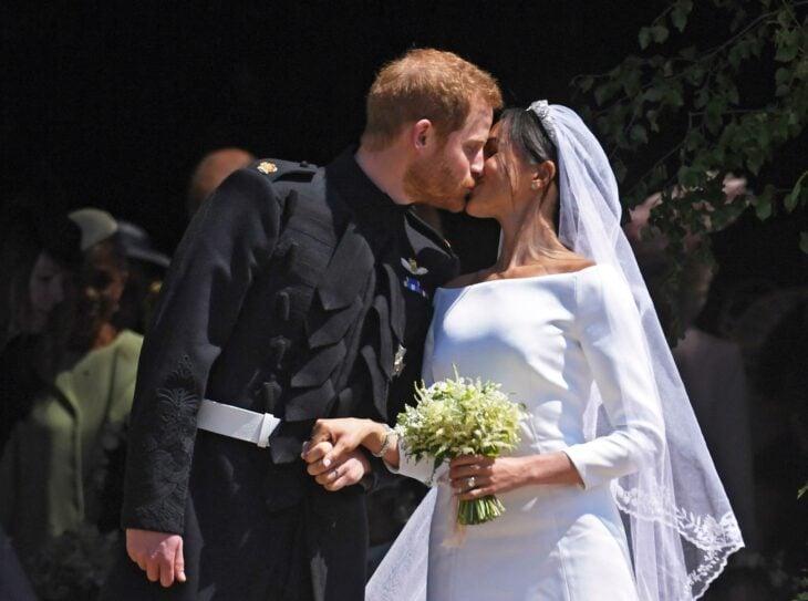 Meghan Markle el día de su boda luciendo un vestido blanco de encaje con un ramo de novia con flores blancas