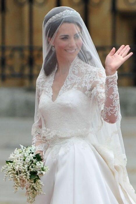 Kate Middleton  el día de su boda luciendo un vestido blanco de encaje con un ramo de novia con flores blancas
