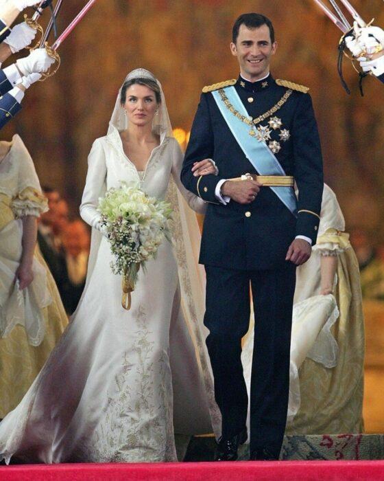 Letizia de España  el día de su boda luciendo un vestido blanco de encaje con un ramo de novia con flores blancas