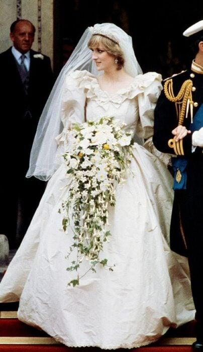 Diana Spencer  el día de su boda luciendo un vestido blanco de encaje con un ramo de novia con flores blancas