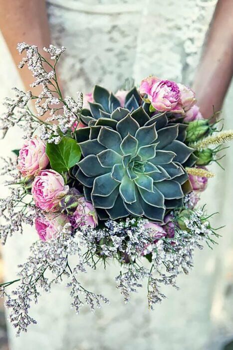 Ramo de novia hecho con una suculenta grande y diferentes rosas rosas y complementos en color plateado