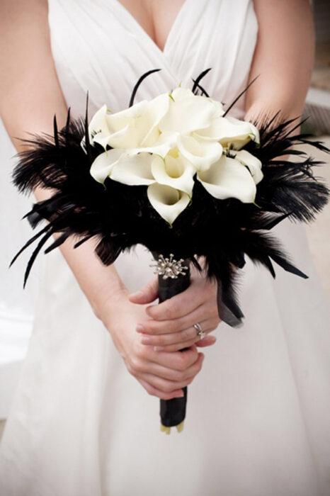 Ramo de novia hecho con plumas de color negro y flores de color blanco