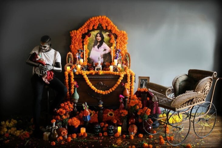 Hombre vestido de catrín posa en altar de muertos que hizo en honor a su esposa mientras sostiene a su bebé en brazos y la mira
