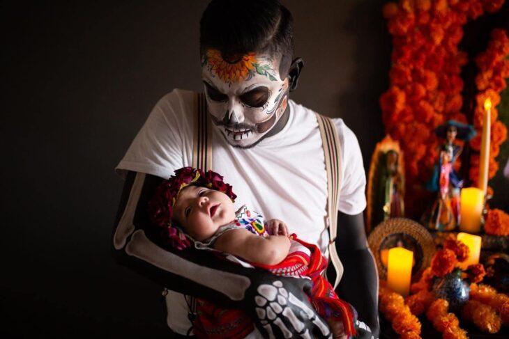 Hombre vestido de catrín posa en altar de muertos que hizo en honor a su esposa mientras sostiene a su bebé en brazos