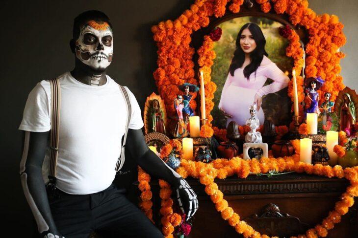 Hombre vestido de catrín posa en el altar que le hizo a su esposa fallecida
