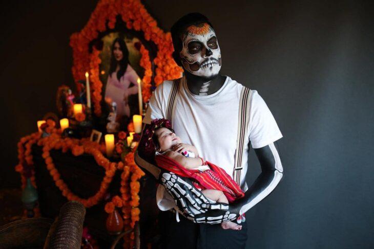 Hombre vestido de catrín posa en altar de muertos que hizo en honor a su esposa mientras sostiene a su bebé en brazos y mira por la ventana