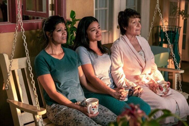 escena de la serie Jane The Virgin con tres chicas sentadas en un sofá