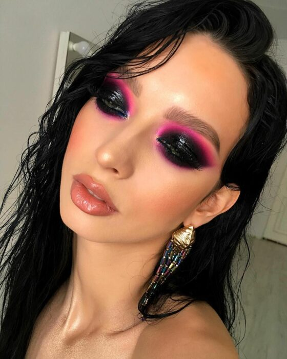 Girl with eyes made up in the style of Smoke Eyes with a line in neon pink color