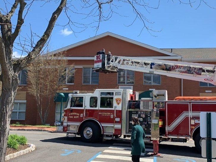 Camión de bomberos subiendo a un hombre en grúa