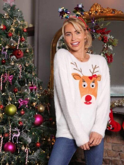 Chica con suéter navideño en blanco decorado con un reno