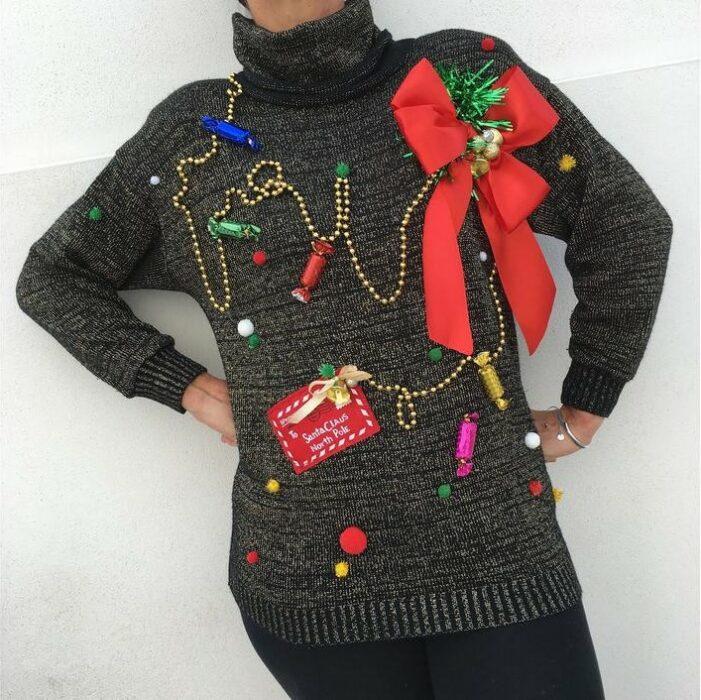 Chica con suéter navideño en tono negro decorado con guias y moños