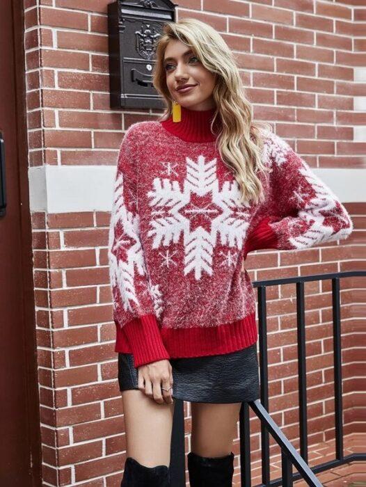 Chica con suéter navideño en rojo decorado con un copo de nieve gigante