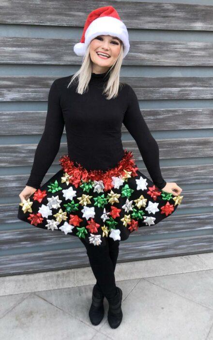 Chica con falda navideña en tono negro con moños de regalo