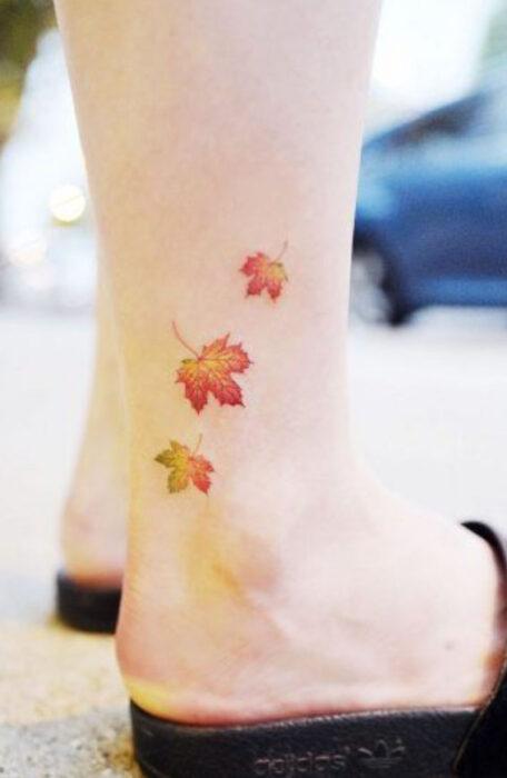 Tatuaje pequeño sobre el tobillo de tres hojitas de maple en otoño