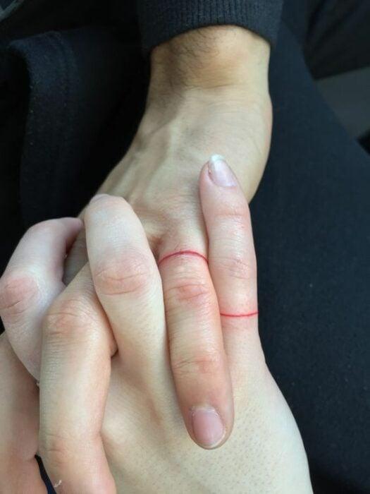 Tatuaje complementario de un hilo rojo atado sobre el dedo pulgar de la mano