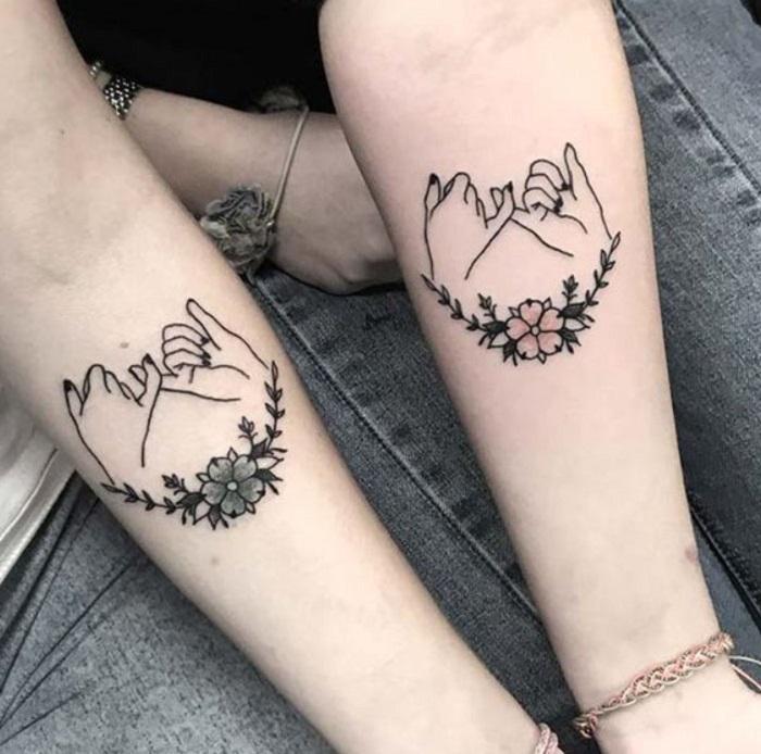 Tatuaje complementario de manitas haciendo pinky promise sobre la zona del antebrazo
